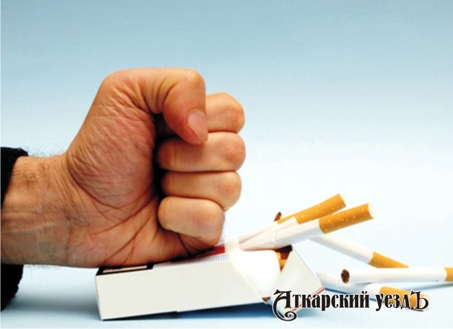 Мужчина давит пачку с сигаретами