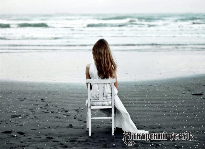 Женщина сидит на берегу моря