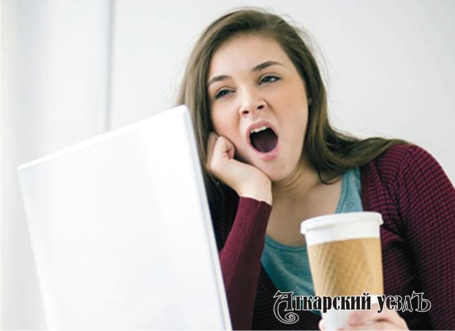 Девушка зевает с чашкой кофе